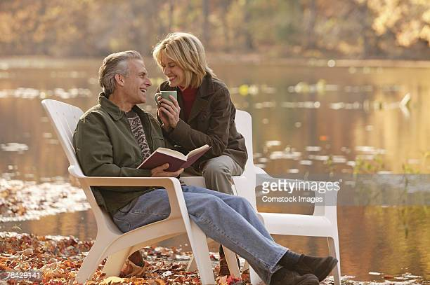 Couple sitting by lake in autumn