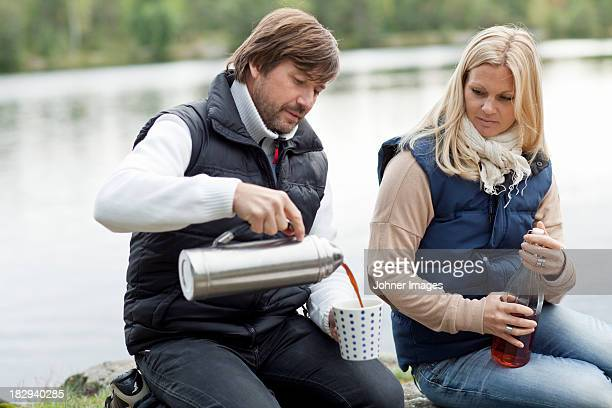 Couple sitting by lake with hot coffee and lemonade