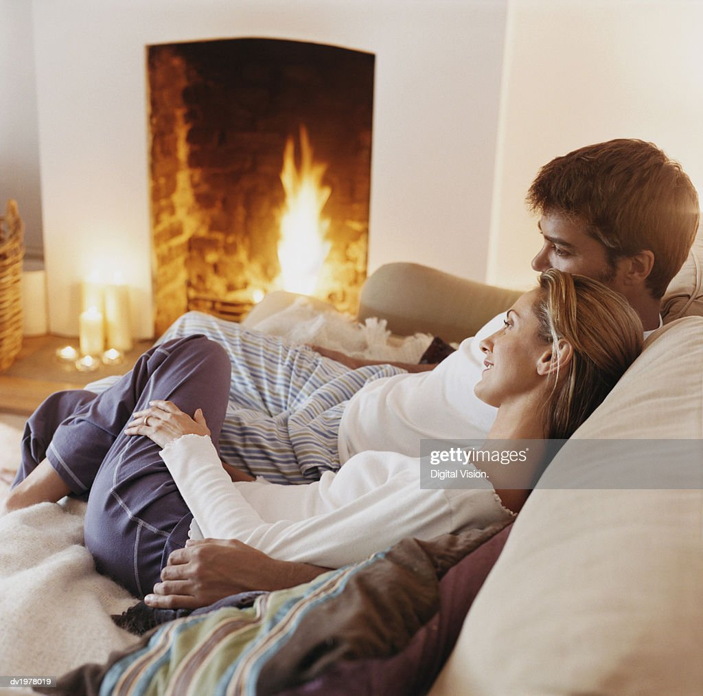 Couple Sitting Close to Each Other on a Sofa by a Fireplace : Stock Photo