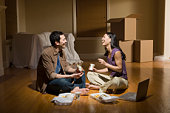 Couple sitting cross-legged on living room, eating take out food, laughing, side view