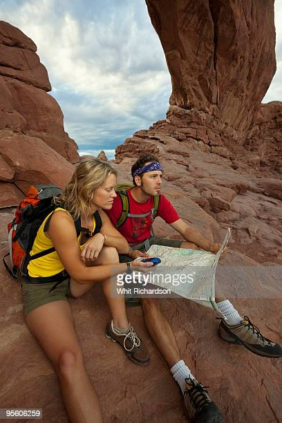 A couple sitting down in front of an arch using a GPS and a map in Arches National Park, Utah.