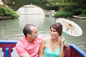 Couple sitting in a boat with parasol