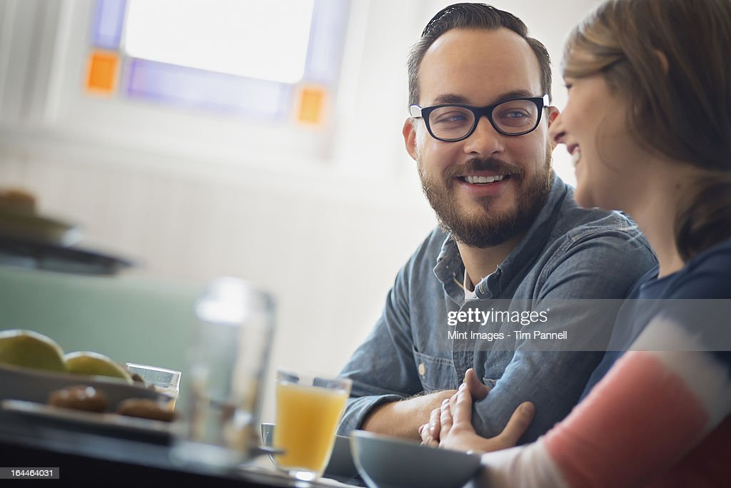 A couple sitting in a coffee shop smiling and talking over a cup of coffee. : Stock Photo