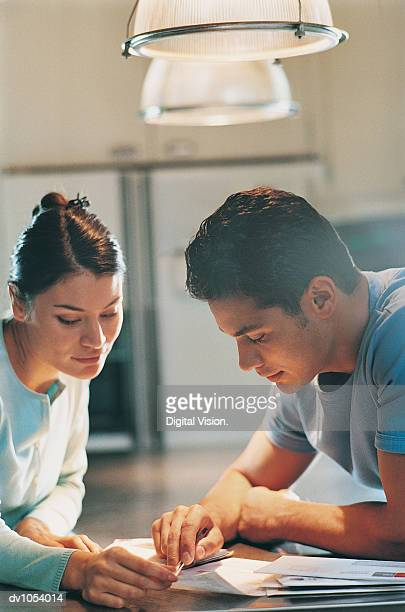 Couple Sitting in a Kitchen Organising their Personal Finances