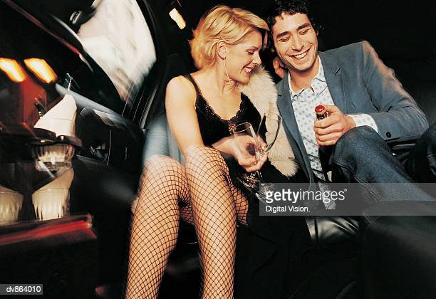 Couple Sitting in a Limousine, Man Opening Champagne