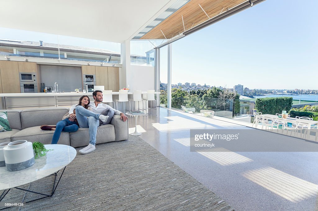 Couple sitting in a modern open plan house. : Stock-Foto