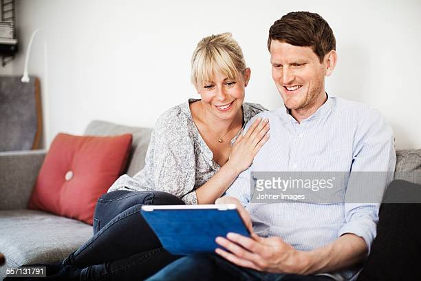 A couple sitting in a sofa with a tablet