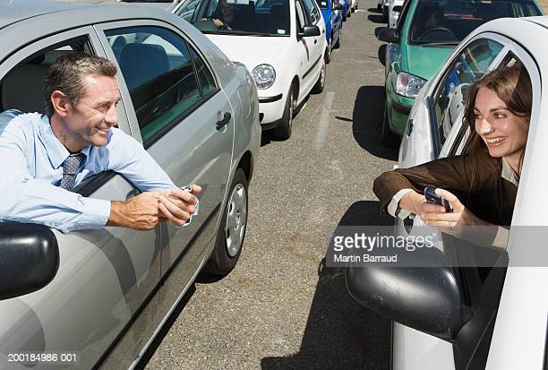 Couple sitting in adjacent cars in traffic jam, holding mobile phones