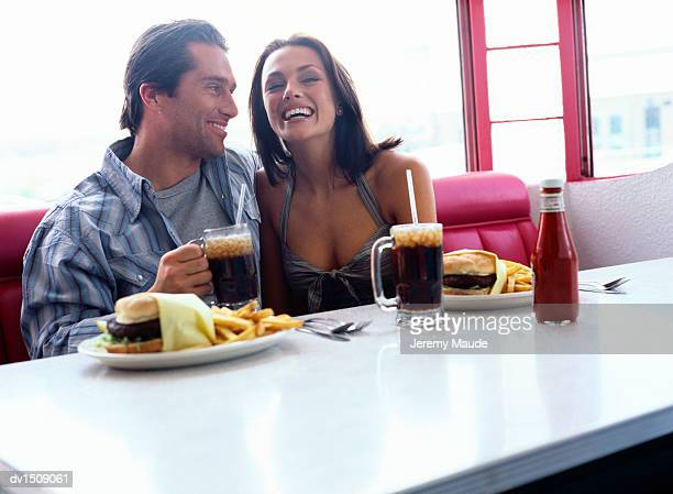 Couple Sitting in an American Diner Eating Hamburger and Chips With Cola