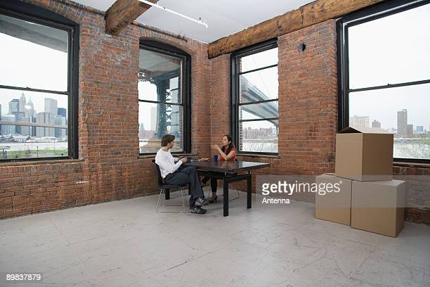 Couple sitting in an empty loft apartment