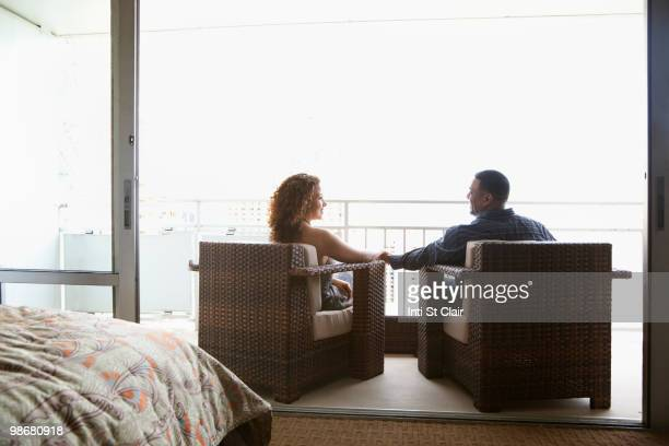 Couple sitting in armchairs and holding hands on urban balcony