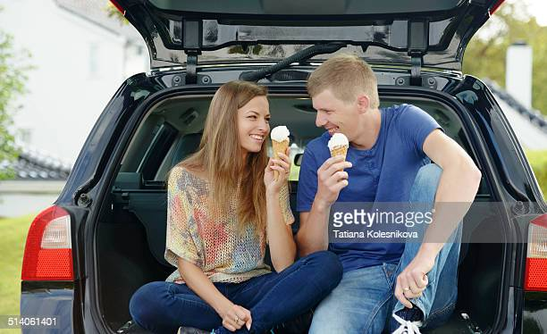Couple sitting in back of car and eating ice cream