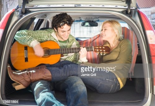 Couple sitting in back of car with guitar
