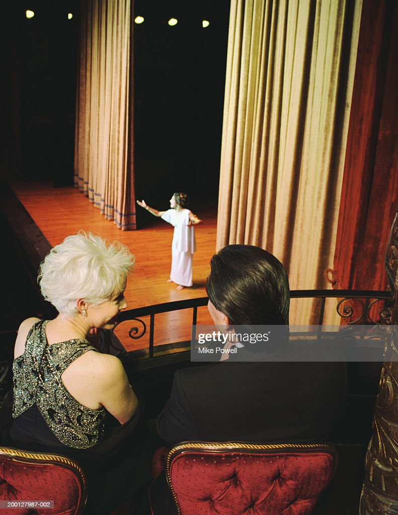 Couple sitting in balcony seats at opera, rear view