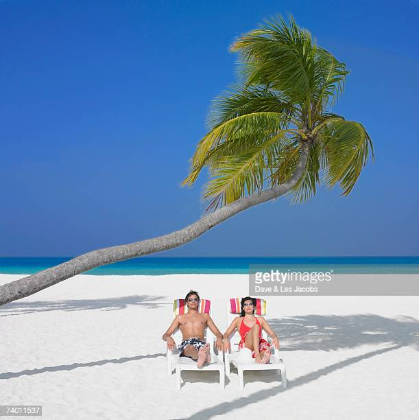 Couple sitting in beach chairs under palm tree