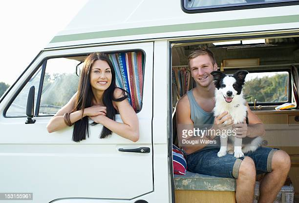Couple sitting in camper with pet dog.