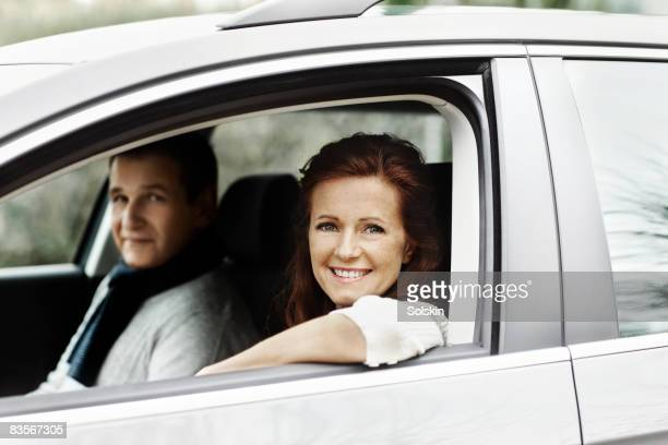 Couple sitting in car, looking out