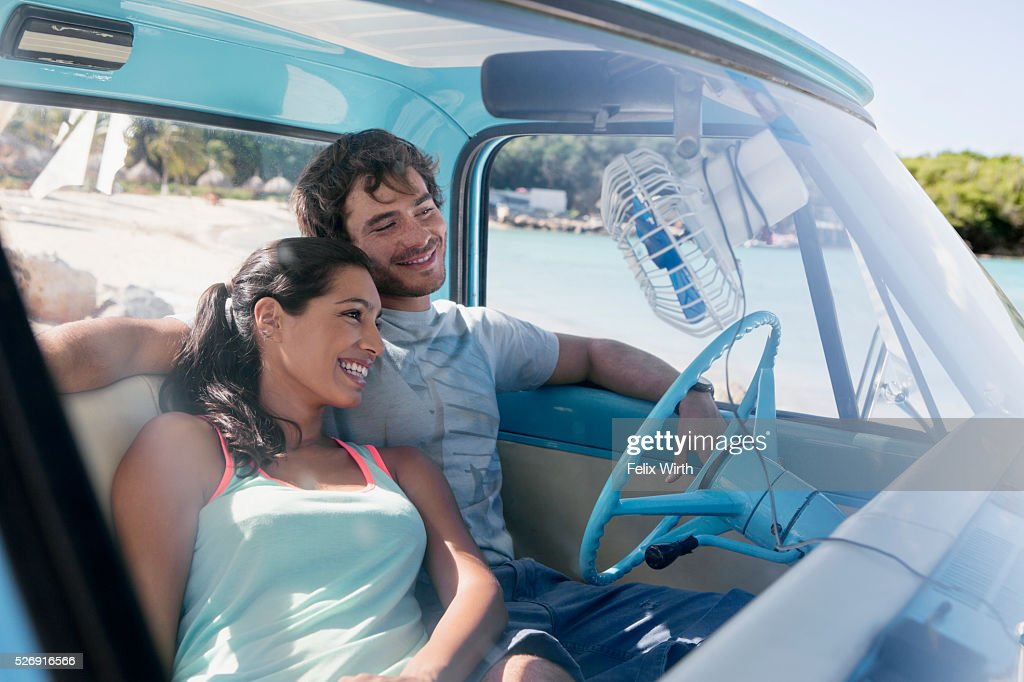 Couple sitting in car on beach : Stockfoto