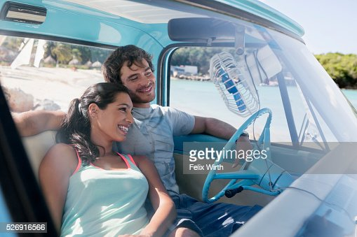 Couple sitting in car on beach : ストックフォト
