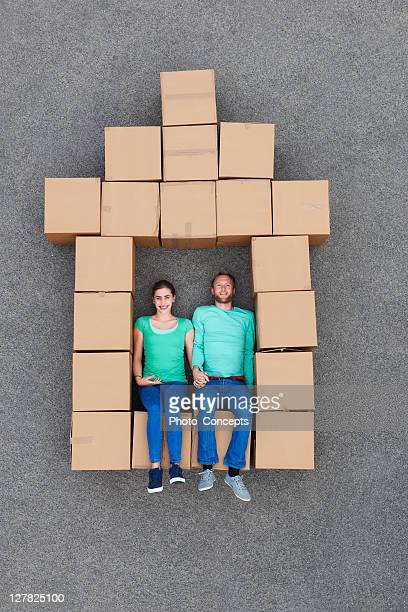 Couple sitting in cardboard box house