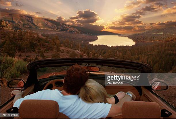 Couple sitting in convertible car looking at view in Maldives