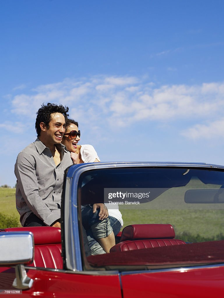 Couple sitting in convertible, laughing : Stock Photo