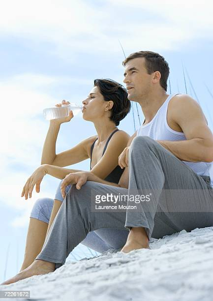 Couple sitting in exercise clothing on beach, woman drinking water