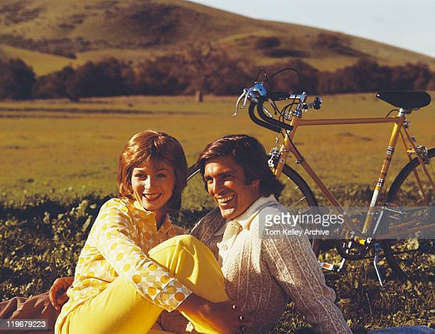 Couple sitting in field with bicycle, smiling