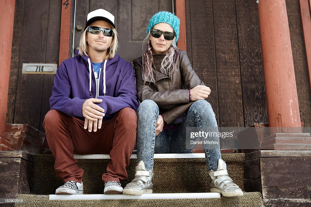 Couple sitting in front of a house. : Stock Photo