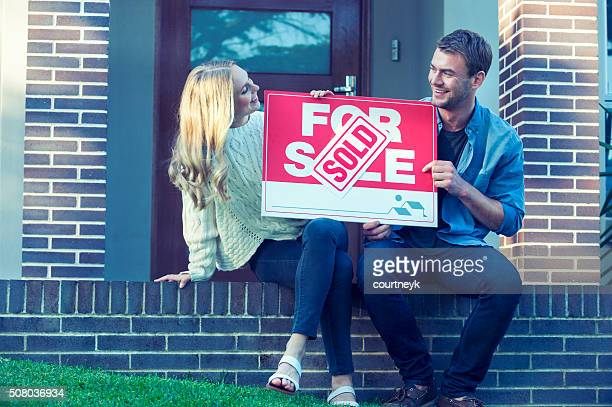 Couple sitting in front of a new home.