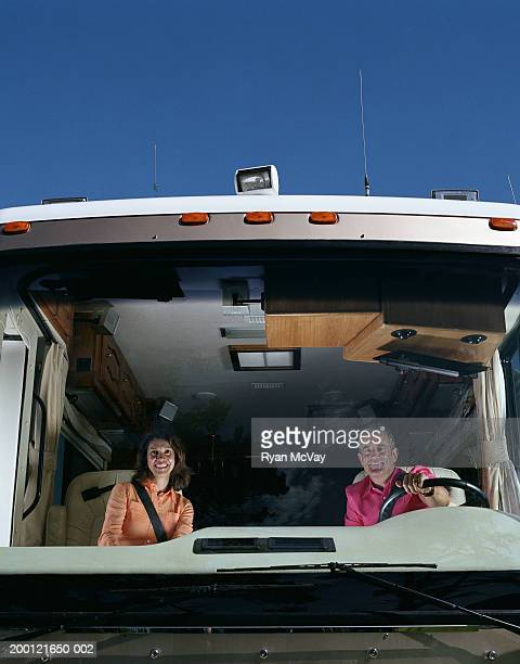 Couple sitting in front seats of motor home, view through windshield