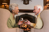 Couple sitting in living room by fireplace with drinks smiling