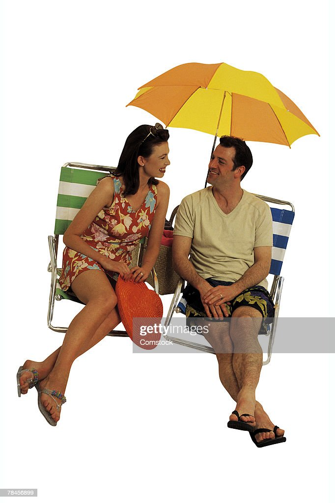 Couple sitting in lounge chairs on vacation : Stock Photo