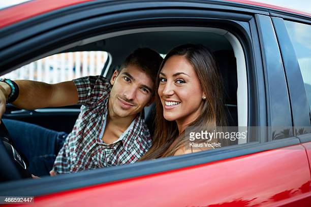 Couple sitting in red car, looking to camera