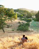 Couple sitting in remote field kissing