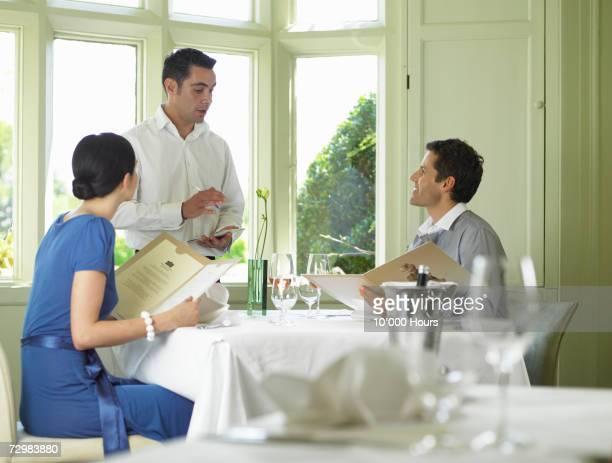 Couple sitting in restaurant listening to waiter