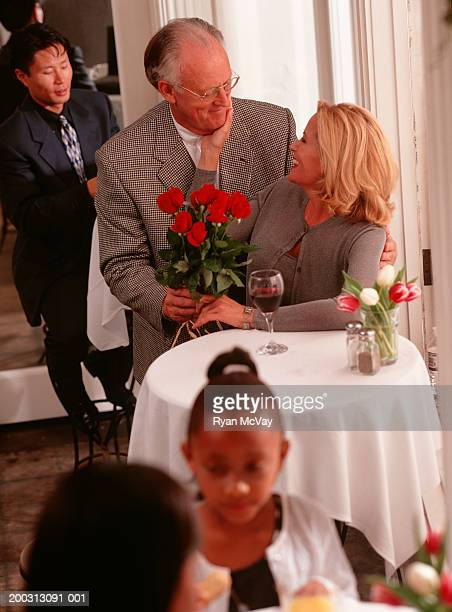 Couple sitting in restaurant, man giving woman bunch of flowers, elevated view
