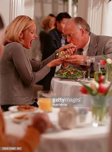 Couple sitting in restaurant, man kissing hand