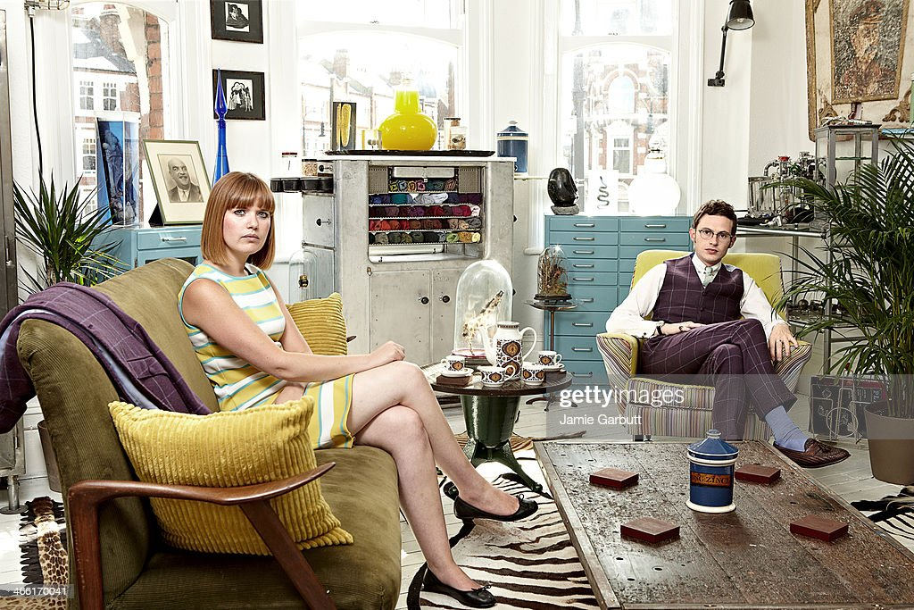 Couple sitting in retro-styled living room. : Stock Photo