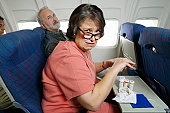 Couple Sitting in Seats in an Aeroplane Cabin, Woman With Pills