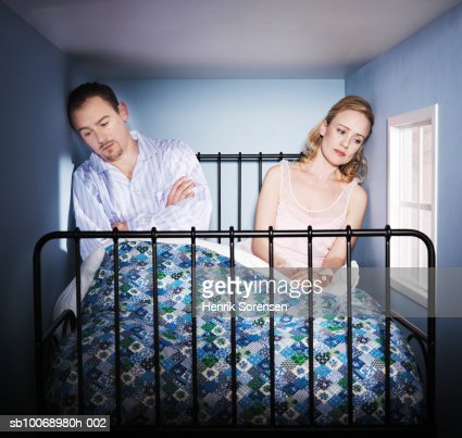 Couple sitting in small bed room, looking depressed