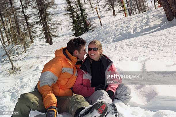 Couple sitting in snow, laughing