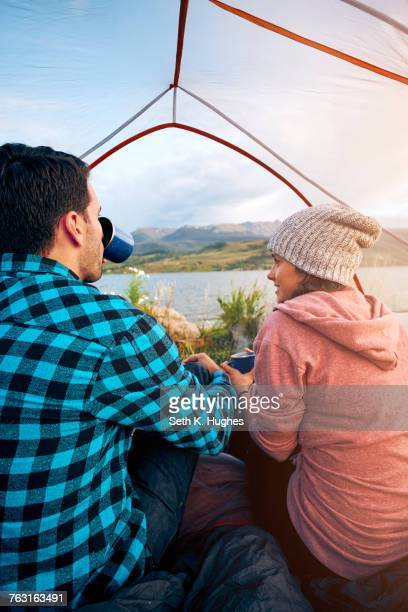 Couple sitting in tent, drinking hot drinks, looking out at view, Heeney, Colorado, United States