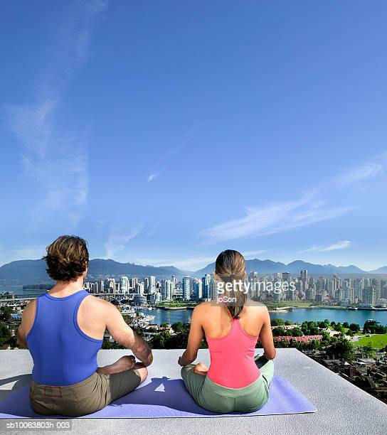 Couple sitting in yoga position, rear view