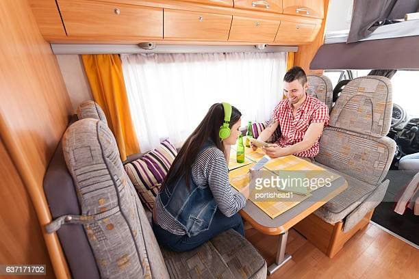 Couple sitting inside of a camper and using smart phones
