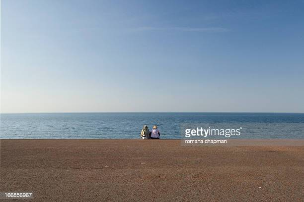 couple sitting, looking out at sea