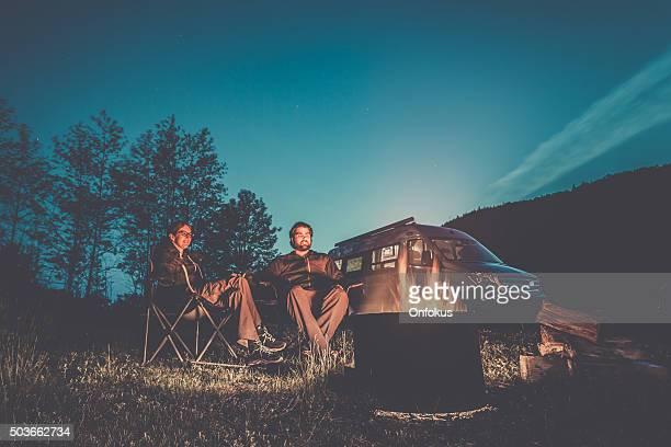 Couple assis près de feu de camp avec camping-car Van