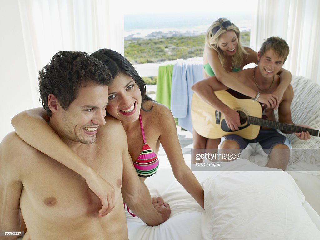 A couple sitting on a bed and another couple with an acoustic guitar : Stock Photo