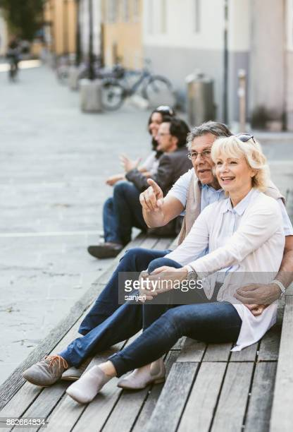 Couple Sitting on a Bench Along The City Street