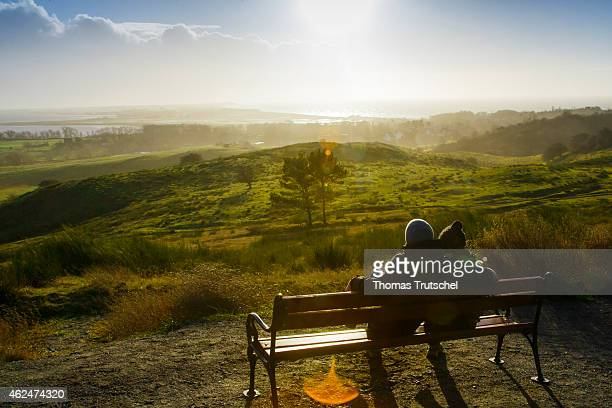 Couple sitting on a bench on a hill and viewing over the Island Hiddensee January 02 2015 in Kloster Germany Hiddensee is a carfree island in the...